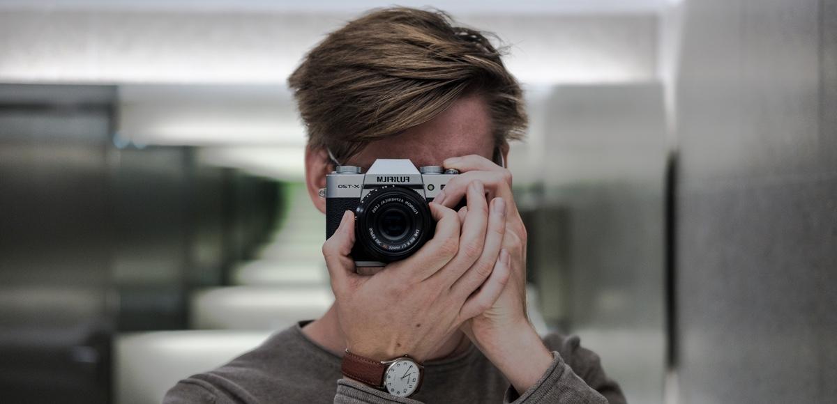 Symbolbild: ein Mann fotografiert sich selbst in einem Spiegel