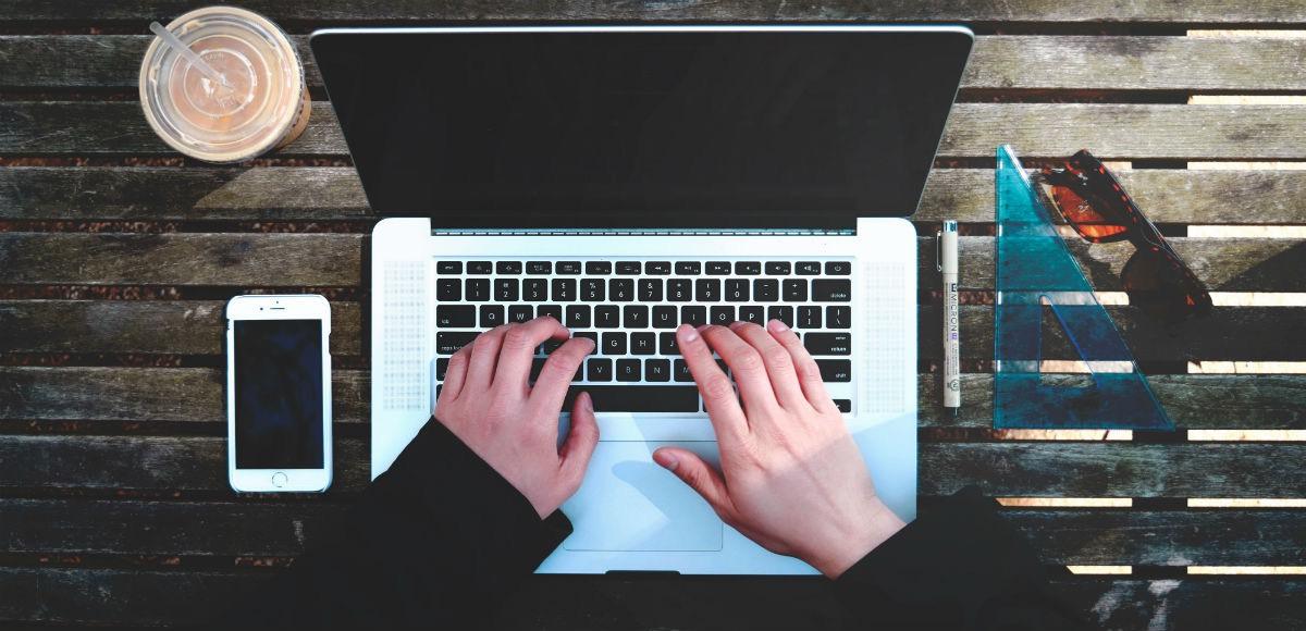 Symbolbild: Ein Notebook auf einem Holz-Gartentisch mit einem Handy daneben