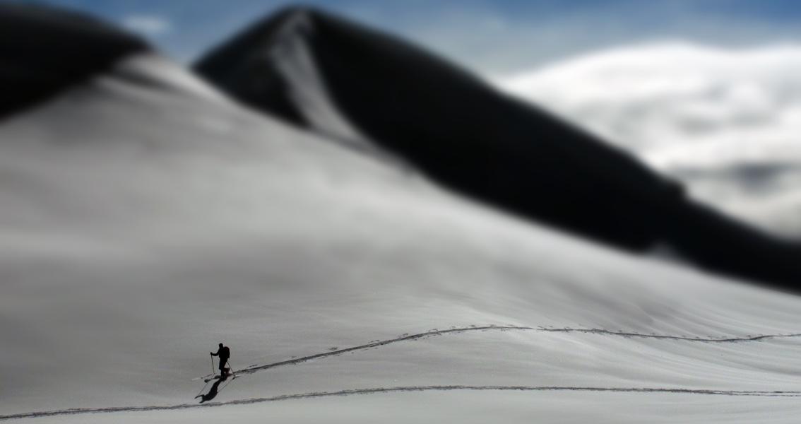 Symbolbild: eine Person wandert auf einem schneebedeckten Berg