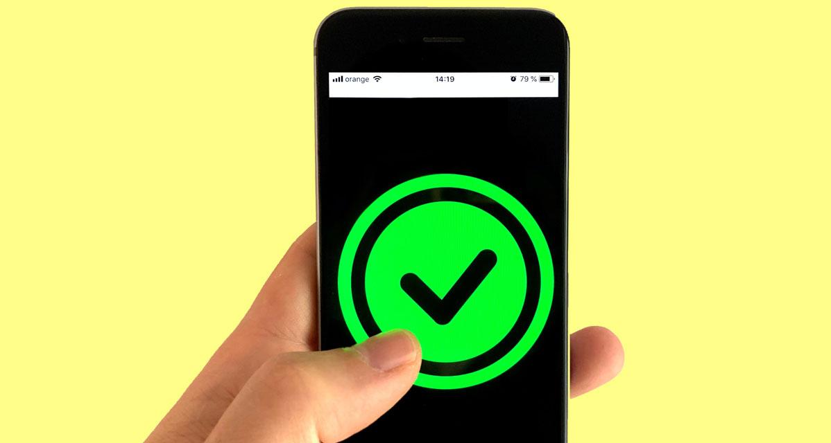 Symbolbild: Smartphone mit einem grünen Haken, der von einem Daumen gedrückt wird
