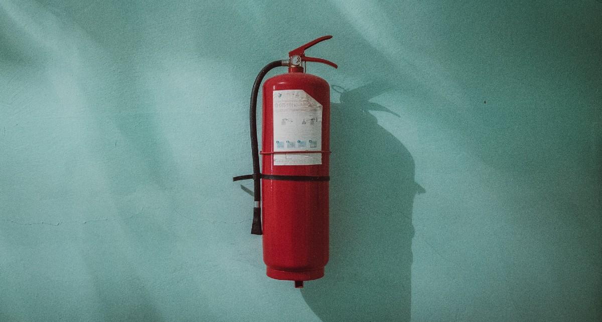 Roter Feuerlöscher an grüner Wand